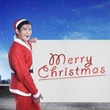 Equipe o traje vestindo de Papai Noel que guarda a bandeira com escrita do Feliz Natal Foto de Stock
