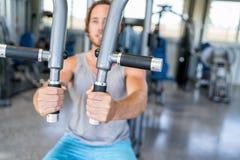 Equipe o treinamento da força na máquina da aptidão no gym foto de stock