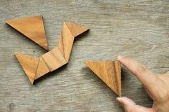Equipe o triângulo da posse para cumprir o enigma do tangram na forma do pássaro Fotografia de Stock