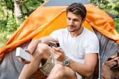 Equipe o turista que usa o telefone celular e o mini orador portátil Imagens de Stock