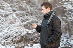 Equipe o uso um telefone na natureza um o dia do ` s do inverno Fotografia de Stock Royalty Free
