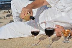 Equipe o vinho tinto de derramamento da garrafa em um vidro na praia Imagem de Stock Royalty Free