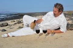 Equipe o vinho tinto de derramamento da garrafa em um vidro na praia Imagem de Stock