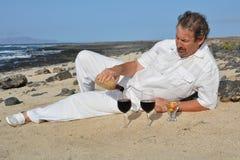 Equipe o vinho tinto de derramamento em dois vidros na praia Imagem de Stock Royalty Free