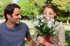 Equipe a observação de seu amigo cheirar um grupo de flores Fotos de Stock Royalty Free