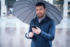 Equipe a observação no smartphone da previsão de tempo em um dia chuvoso fotografia de stock royalty free