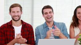 Equipe ocasional do negócio que aplaude durante a reunião video estoque