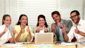 Equipe ocasional do negócio que mostra os polegares até a câmera durante a reunião