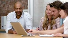 Equipe ocasional do negócio que tem uma reunião usando o portátil vídeos de arquivo
