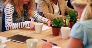 Equipe ocasional do negócio que toma a nota durante a reunião video estoque