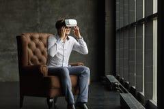 Equipe os óculos de proteção vestindo da realidade virtual que olham filmes ou que jogam jogos de vídeo O projeto dos auriculares fotografia de stock royalty free