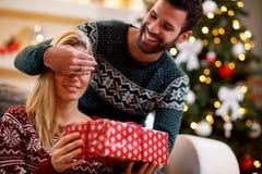 Equipe os olhos do ` s da mulher da coberta com mãos e caixa de presente da doação imagens de stock