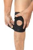 Equipe os pés com um joelho em uma cinta de joelho protetora Imagens de Stock Royalty Free