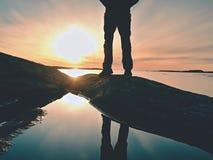 Equipe os pés do caminhante nas botas altas espelhadas na associação de água, mar com sol do por do sol Figura do turista em roch Fotografia de Stock
