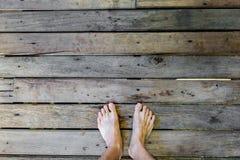 Equipe os pés do ` s na madeira velha da prancha Imagem de Stock Royalty Free