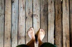 Equipe os pés do ` s na madeira velha da prancha Fotos de Stock Royalty Free