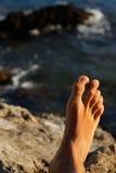 Equipe os pés que relaxam em feriados em uma praia ou em um lago com o wa do mar Imagens de Stock Royalty Free
