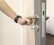 Equipe os puxadores da porta da captura de aço inoxidável na madeira da porta para abrir Fotos de Stock Royalty Free