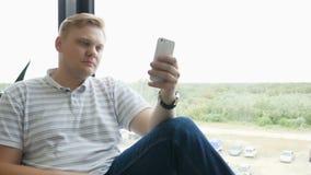 Equipe os sms que texting usando o app no telefone esperto na noite na cidade Homem de negócio novo considerável que usa o sorris video estoque