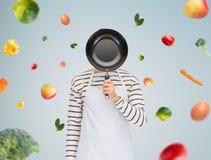 Equipe ou cozinhe na cara escondendo do avental atrás da frigideira Fotografia de Stock Royalty Free