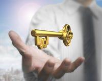 Equipe a palma que guarda a chave dourada do tesouro da forma do dólar Fotografia de Stock Royalty Free