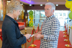 Equipe a passagem do bilhete à mulher no teatro da entrada Fotos de Stock Royalty Free