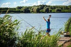 Equipe peixes com o equipamento de giro no cais de madeira fotografia de stock
