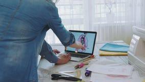 Equipe pequena dos desenhadores de moda que escolhem esboços no laptop video estoque