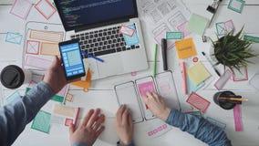 Equipe pequena dos desenhistas de UX que discutem o wireframe do app video estoque