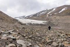 Equipe a pesquisa por fósseis em uma moraine rochosa da geleira de Longyear em Svalbard, Noruega A borda da geleira no fundo foto de stock