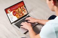Equipe a pizza pedindo pelo Internet com um laptop, sentando-se em casa foto de stock royalty free