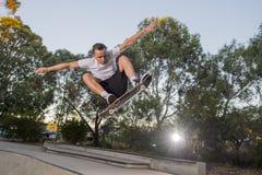 Equipe a placa radical praticando do patim que salta e que aprecia truques e conluios na trilha de patinagem da meia tubulação co Imagens de Stock