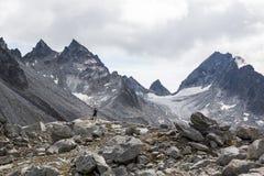 Equipe a posição abaixo do cirque enorme, da geleira, e dos picos rochosos no Imagens de Stock Royalty Free