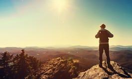 Equipe a posição na borda de um penhasco que negligencia as montanhas Fotografia de Stock Royalty Free