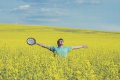 Equipe a posição no prado amarelo da colza com mãos levantadas Conceito da liberdade e da felicidade Imagens de Stock Royalty Free