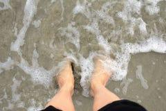 Equipe a posição no seu com os pés descalços na praia Imagem de Stock