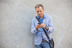Equipe a posição pela parede e smartphone da utilização Fotos de Stock Royalty Free
