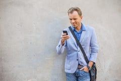 Equipe a posição pela parede e a vista de seu telefone Imagem de Stock Royalty Free