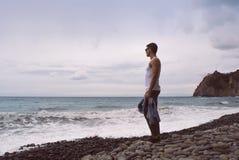 Equipe a posição pelas ondas do oceano em uma praia rochosa imagens de stock royalty free