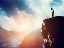 Equipe a posição com o portátil no pico de uma montanha Fotografia de Stock Royalty Free