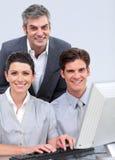 Equipe positiva do negócio que trabalha em um computador Imagens de Stock Royalty Free
