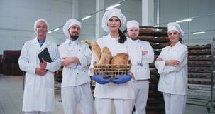 Equipe principal da fábrica da padaria dos padeiros e do coordenador em um grande humor que olha em linha reta à câmera e ao sorr video estoque