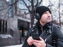 Equipe a procura de um lugar usando o mapa de GPS no smartphone Perdeu em cidade desconhecida é vestido em um casaco de cabedal,  Imagem de Stock Royalty Free