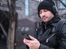 Equipe a procura de um lugar usando o mapa de GPS no smartphone Perdeu em cidade desconhecida é vestido em um casaco de cabedal,  Imagens de Stock