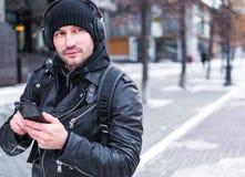Equipe a procura de um lugar usando o mapa de GPS no smartphone Perdeu em cidade desconhecida é vestido em um casaco de cabedal,  Imagem de Stock