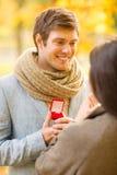 Equipe a proposição a uma mulher no parque do outono Fotos de Stock