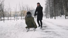 Equipe puxar a menina em um trenó na neve vídeos de arquivo