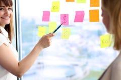 Equipe que trabalha com etiquetas no escritório, mulher do negócio que mostra ao sinal de dólar Fotografia de Stock Royalty Free