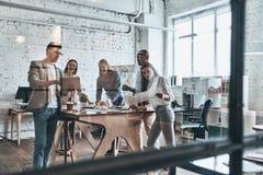 Equipe que trabalha junto Grupo de povos modernos novos no cas esperto imagens de stock