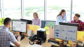 Equipe que trabalha no escritório Monitore a datilografia e o projeto novo que discutem imagem de stock